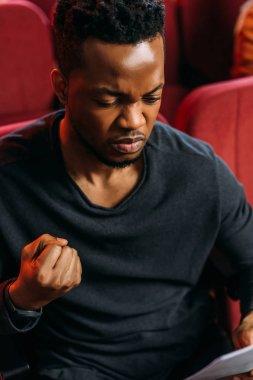 Aggressive african american actor reading scenario during rehearse stock vector