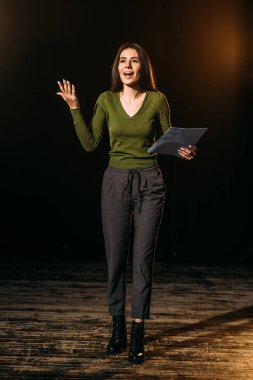 emotional actress performing role with screenplay on stage in theatre