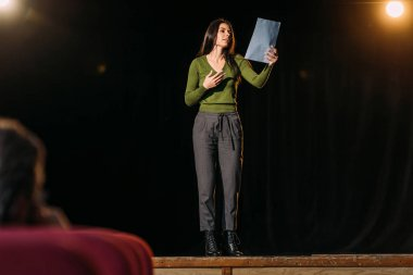 selective focus of theater director and attractive actress reading screenplay on stage