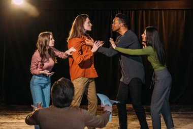 multicultural actors and actresses rehearsing fight on stage in theatre
