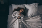 top view of paranormal gothic girl in nightgown lying in bed