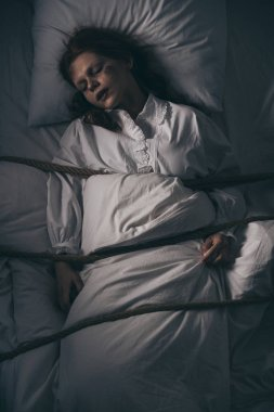 Demonic obsessed sleeping girl in nightgown bound with rope in bed stock vector
