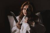 démonická dívka v noční košili drží nůž v posteli