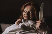démonický úsměv dívka drží nůž v posteli