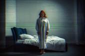 strašidelný démon dívka v noční košili stojící v ložnici s TV šumem