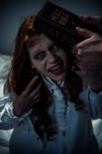 exorcista drží bibli v blízkosti posedlé démonické dívky v ložnici