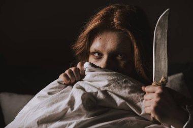 Demonic obsessed evil girl holding knife in bed stock vector