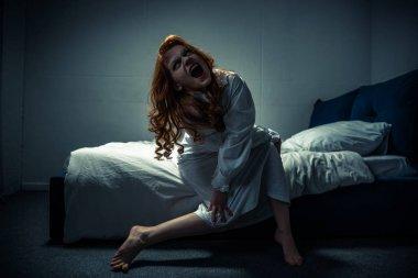 Demonic creepy girl in nightgown shouting in bedroom stock vector