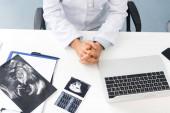 Ausgeschnittene Ansicht einer professionellen Ärztin in der Klinik mit Ultraschalluntersuchungen und Laptop