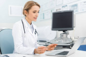 beautiful female doctor working on laptop in clinic with ultrasound scanner