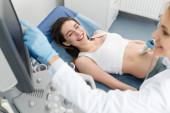 Arzt untersucht Bauch einer glücklichen Schwangeren mit Ultraschall in Klinik