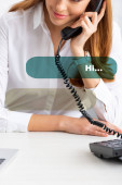 Photo Cropped view of smiling businesswoman talking on telephone near laptop on table, dialog illustration