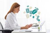 Boční pohled podnikatelky pomocí smartphonu v blízkosti dokumentů a notebooku na stole, e-mailová ilustrace