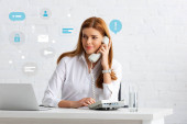 Photo Successful businesswoman talking on phone at table with glass of water and laptop, technology icons illustration