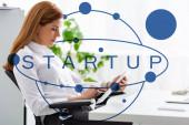 Boční pohled na podnikatelku pomocí digitálního tabletu u stolu v kanceláři, spouštěcí ilustrace