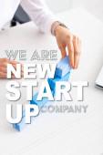 Fényképek Vágott kilátás üzletasszony egymásra kék építőkockák közelében laptop az asztalon, mi vagyunk az új startup cég illusztráció
