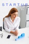 Krásná podnikatelka při pohledu na stohované modré stavební kameny na pracovním stole, startup ilustrace