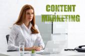 Fotografie Attraktive Geschäftsfrau blickt mit Laptop und Telefon vom Tisch, Content Marketing Illustration