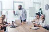 Afrikanisch-amerikanischer Mann zeigt Idee und spricht mit Kollegen bei Treffen in Kreativagentur