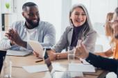 Fotografie selektivní zaměření na usmívající se multikulturní podnikatele mluvící se svými kolegy