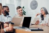 Multikulti-Kollegen sitzen am Tisch und schauen auf digitales Tablet