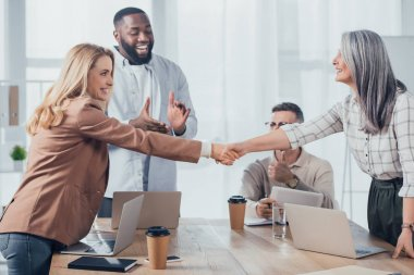smiling multicultural colleagues shaking hands during meeting in creative agency