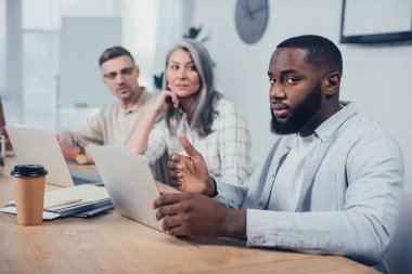 Selective focus of african american man looking at camera and his colleagues looking at him stock vector