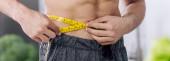 panoramic shot of shirtless man measuring waist