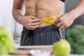 cropped view of shirtless man measuring waist near nutritious food