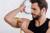 Photo handsome and sportive man measuring muscle on hand