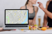 selective focus of laptop with map on screen near couple in kitchen