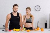 happy man smiling near woman eating sliced orange in kitchen