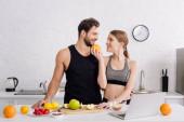 šťastná dívka s pomerančem v blízkosti sportovního muže, notebook a ovoce v kuchyni