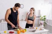 sportovní dívka pití smoothie poblíž muž vaření v kuchyni
