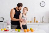 šťastný muž a žena cinkání brýle s smoothie v blízkosti ovoce