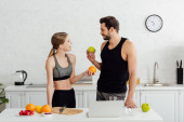 happy man and woman with tasty fruits looking at each other near laptop