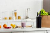 chutné a zralé ovoce v blízkosti smoothie a papírový sáček se salátem v moderní kuchyni