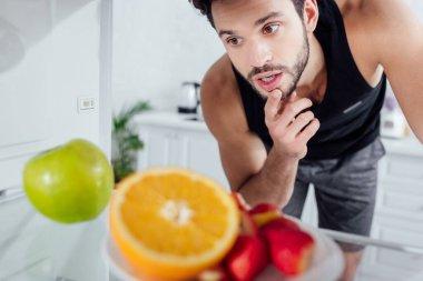 Selective focus of pensive man looking at fruits in fridge stock vector