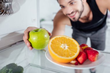 Selective focus of happy man taking apple from fridge stock vector