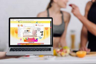 KYIV, UKRAINE - DECEMBER 28, 2019: selective focus of laptop with aliexpress website near couple in kitchen stock vector
