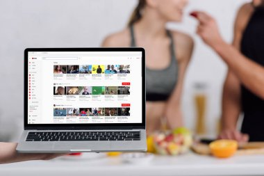 KYIV, UKRAINE - DECEMBER 28, 2019: selective focus of laptop with youtube website near couple in kitchen stock vector