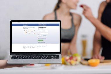 KYIV, UKRAINE - DECEMBER 28, 2019: selective focus of laptop with facebook website near couple in kitchen stock vector