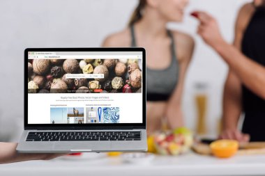 KYIV, UKRAINE - DECEMBER 28, 2019: selective focus of laptop with depositphotos website near couple in kitchen stock vector