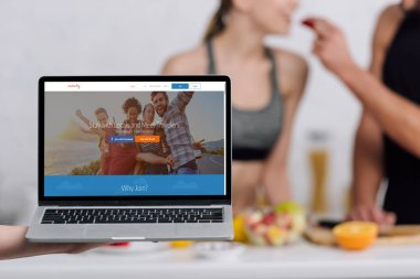 KYIV, UKRAINE - DECEMBER 28, 2019: selective focus of laptop with couchsurfing website near couple in kitchen stock vector