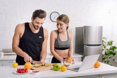 Happy man cutting apple near girl in sportswear and laptop stock vector