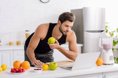 Handsome man using laptop near blender with smoothie and tasty fruits stock vector