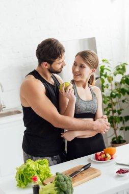 Happy man hugging girl in sportswear with apple stock vector