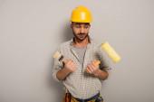 skeptický dělník v klobouku drží váleček barvy a štětec na šedé