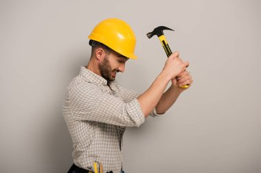 Stressed workman beating yellow helmet with hammer on grey stock vector