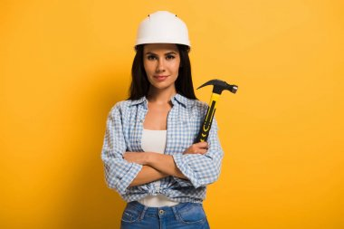 confident female manual worker in helmet holding hammer with crossed arms on yellow